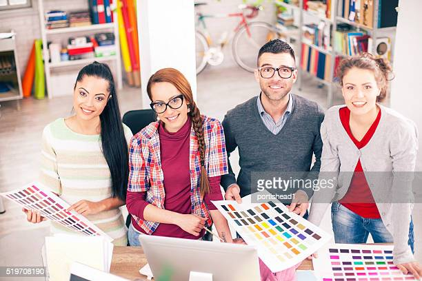 Team of young graphic designers holding color palette at workplace