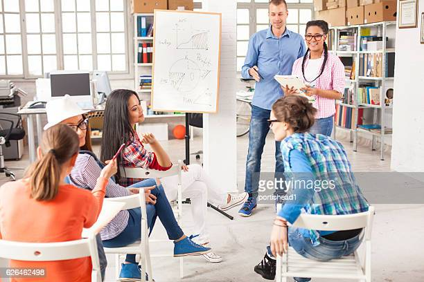 Team of young people making presentation in modern office