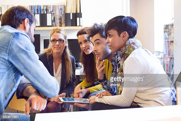 Team of young professionals sitting together in discussion