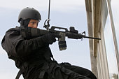 SWAT Team Officer Rappelling and Aiming Gun