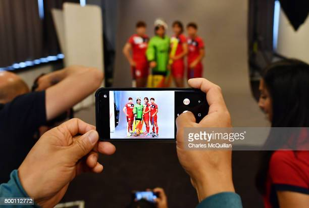 A team official takes a smartphone photograph during a player portrait photo session for FINTRO Hockey World League on June 23 2017 in Brussels...