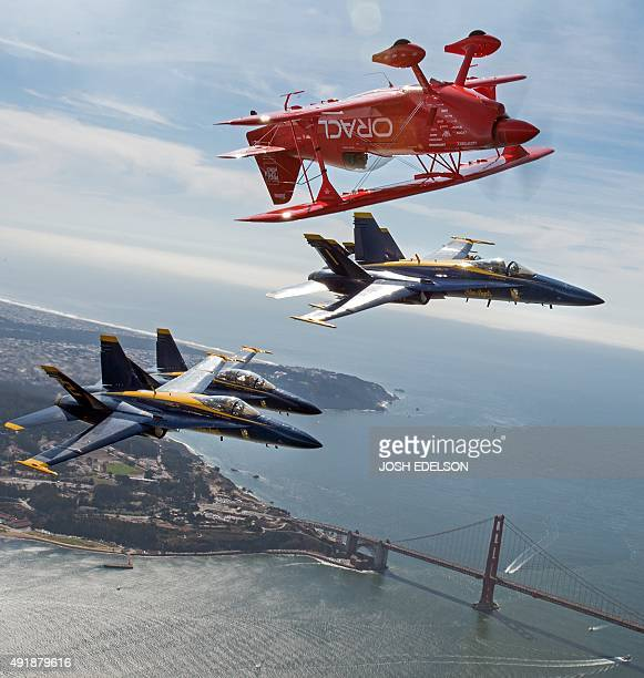 Team Oracle stunt pilot Sean Tucker flies near the Golden Gate Bridge along with three US Navy Blue Angels F/A18 Hornets as part of a practice run...