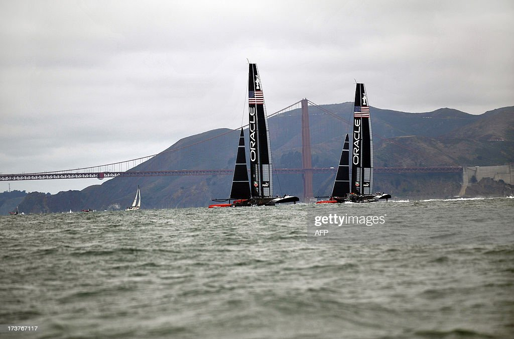 Team Oracle USA sails their two AC-72 Racing Yachts near the Golden Gate Bridge during a training session for the America's Cup race in San Francisco, California on July 17, 2013. Oracle Team USA is not yet allowed to train on the official course as they have not yet met all of the mandated safety requirements for the competition. AFP PHOTO/Josh EDELSON
