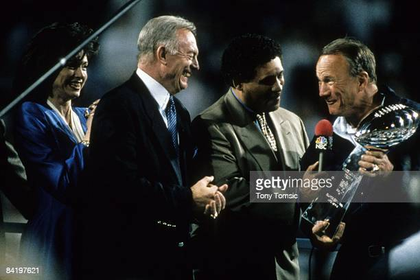 Team owner Jerry Jones of the Dallas Cowboys celebrates with head coach Barry Switzer as he is interviewed by Greg Gumbel of NBC Sports after Super...
