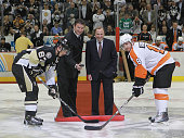 Team owner Mario Lemieux of the Pittsburgh Penguins drops the puck between Sidney Crosby of the Penguins and Mike Richards of the Philadelphia Flyers...