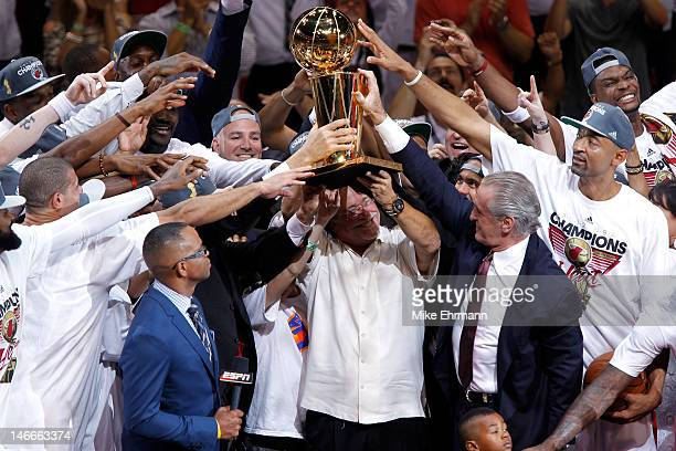 Team owner Micky Arison of the Miami Heat holds up the Larry O'Brien Championship trophy as he celebrates with his players after they won 121106...