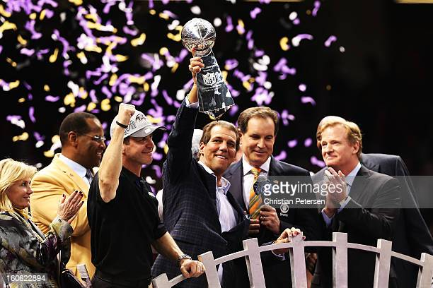 Team owner Steve Bisciotti of the Baltimore Ravens holds up the Vince Lombardi trophy as he celebrates with head coach John Harbaugh after they won...
