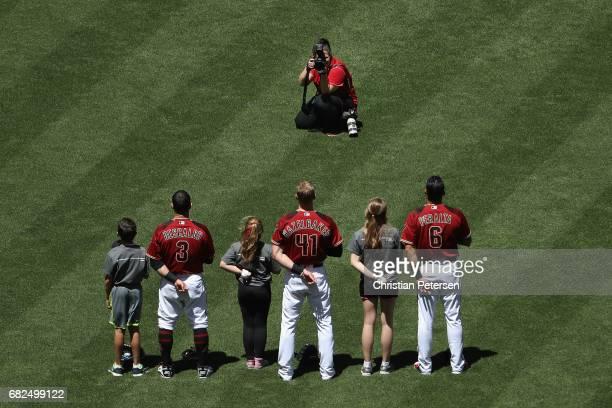 Team photographer Sarah Sachs photographs Daniel Descalso Jeremy Hazelbaker and David Peralta of the Arizona Diamondbacks as they stand with kids for...