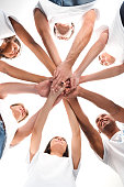 bottom view of multiethnic group of volunteers making team gesture isolated on white