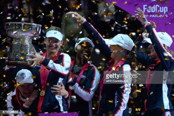 US team pose with their trophy after the Fed Cup final tennis match between Belarus and the United States in Minsk on November 12 2017 / AFP PHOTO /...