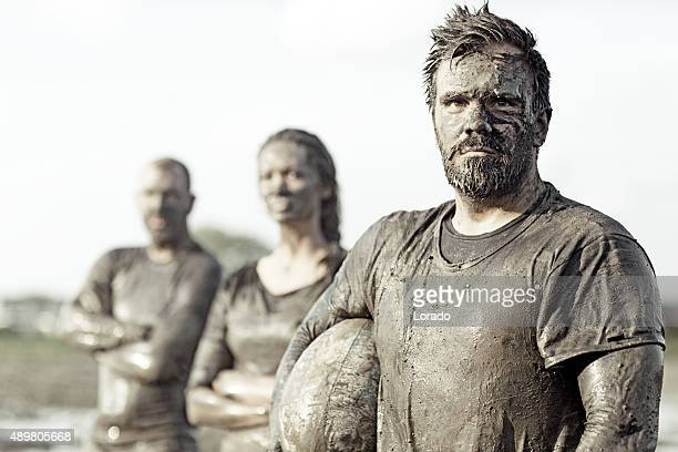 Team posing for a group pic in the mud