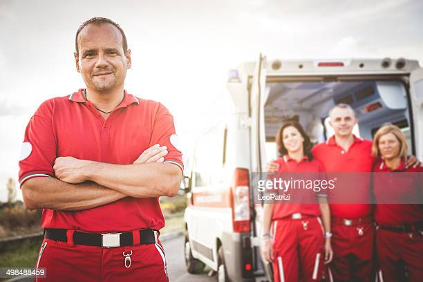 EMT team posing in front of an ambulance