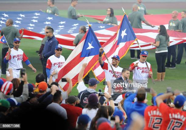 Team Puerto Rico catcher Yadier Molina and designated hitter Carlos Beltran lead there team onto the field while holding the flag of Puerto Rico...