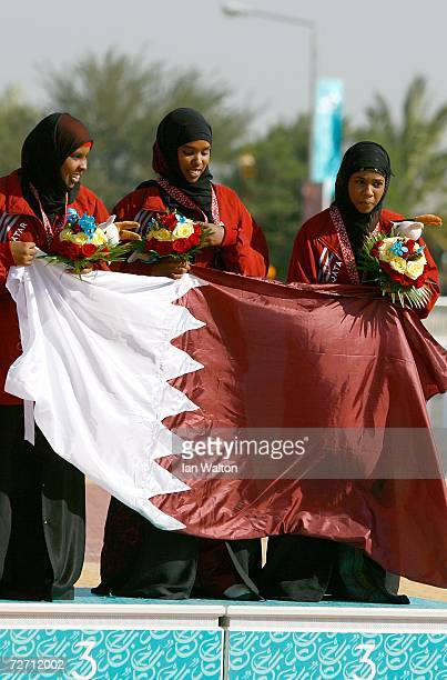 Team Qatar hold their countries flag after winning the Bronze Medal for Women's 10m Running Target during the 15th Asian Games Doha 2006 at the...