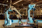 Team robots are test run welding in car factory