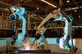 Team robots are welding assembly  part in factory