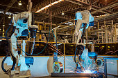 Team robots are welding part in automotive industrial factory