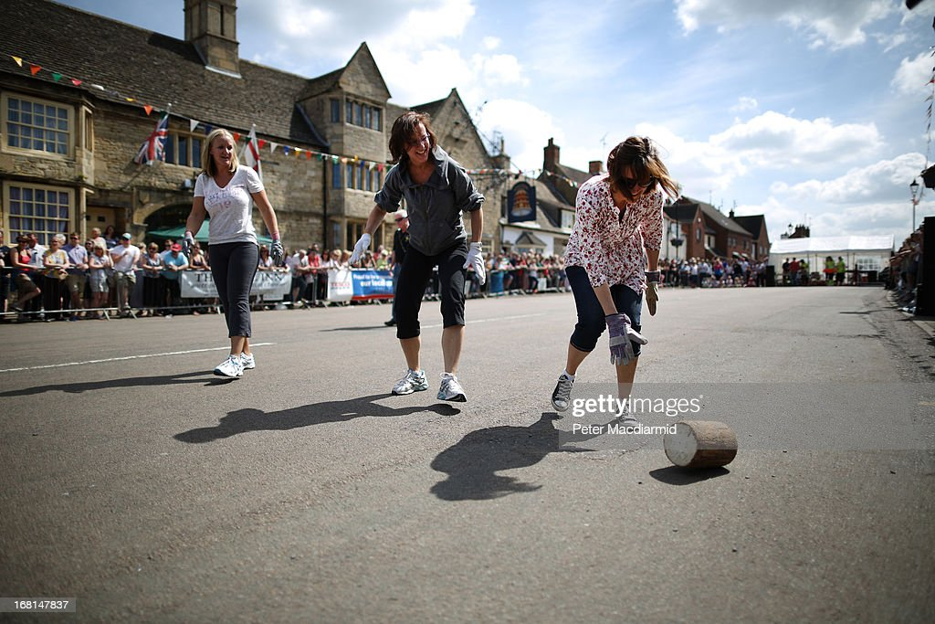 A team roll a wooden 'cheese' during the Stilton Village Festival cheese rolling competition on May 6, 2013 in Stilton, England. Local people are currently involved in a campaign to bring Stilton cheese making back to the village. The cheese is currently made in the counties of Nottinghamshire, Leicestershire and Derbyshire .