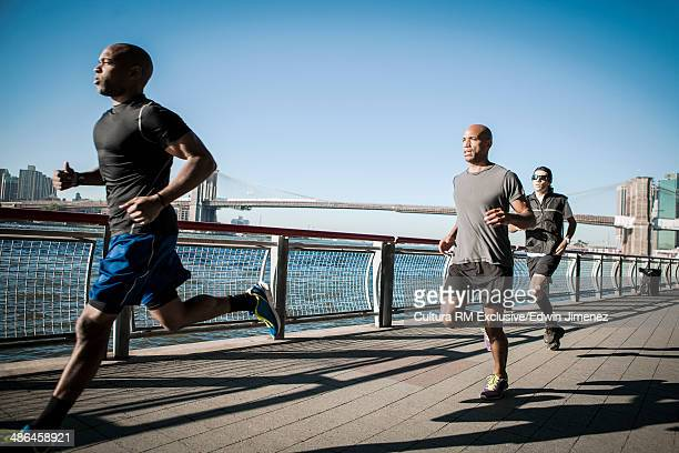 Team running together along waterfront, New York, USA