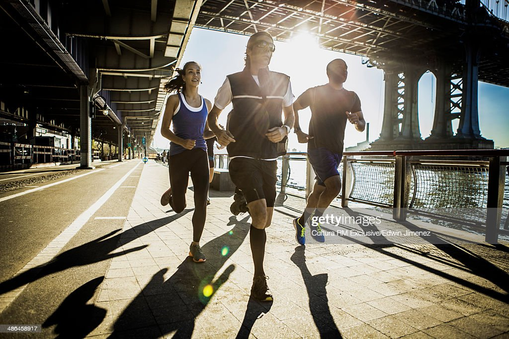 Team running together on bridge, New York, USA : Stock Photo