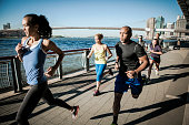 Team running together on waterfront, New York, USA