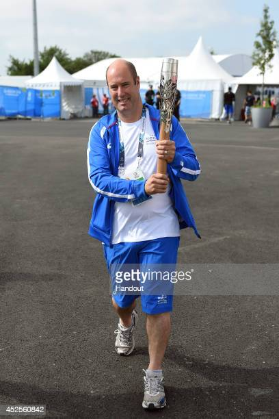 Team Scotland chef de mission Jon Doig carries the Glasgow 2014 Queen's Baton through the Commonwealth Games Athletes' Village on July 23 2014 in...