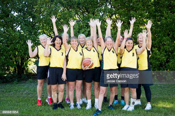 Team shot of senior female basketball players smiling with arms in the air