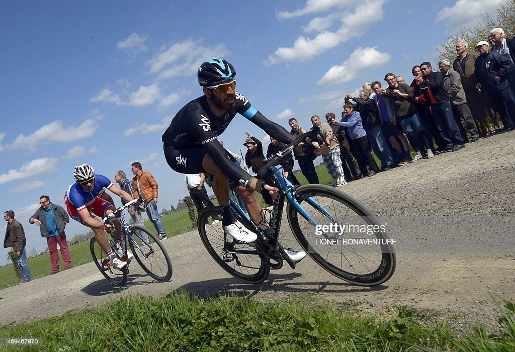 Team Sky British cyclist Bradley Wiggins (R) and FDJ team French cyclist Arnaud Demare (L) ride during the 113th edition of the Paris-Roubaix Paris-Roubaix one-day classic cycling race in Wallers on April 12, 2015.