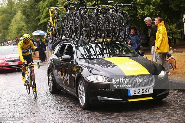 Team Sky cyclist Chris Froome celebrates winning the 2015 Tour de France alongside the Jaguar Sportbrake support car on July 26 2015 in Paris France
