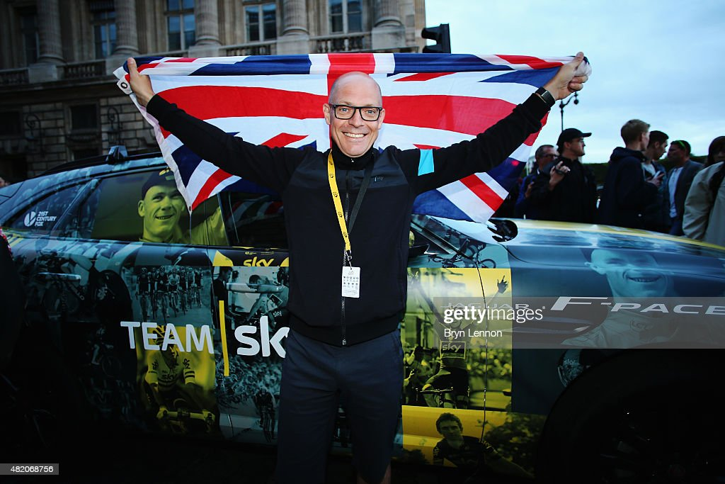 Team Sky manager Sir David Brailsford celebrates Chris Froome's victory in the 2015 Tour de France in front of a special celebratory Jaguar F-PACE car on July 26, 2015 in Paris, France. The specially designed camo on the Jaguar F-PACE features a collection of inspirational Tour images of Froome and the Team Sky riders as well as the UCI yellow race leader stripe.