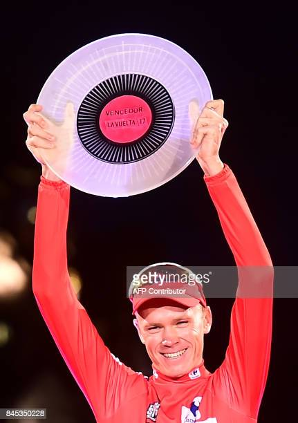 Team Sky's British cyclist Chris Froome raises his trophy as he celebrates on the podium winning the 72nd edition of 'La Vuelta' Tour of Spain...