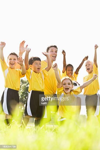 Teamgeist, glückliche junge Fußball spielende Kinder mit Trainer jubeln victory