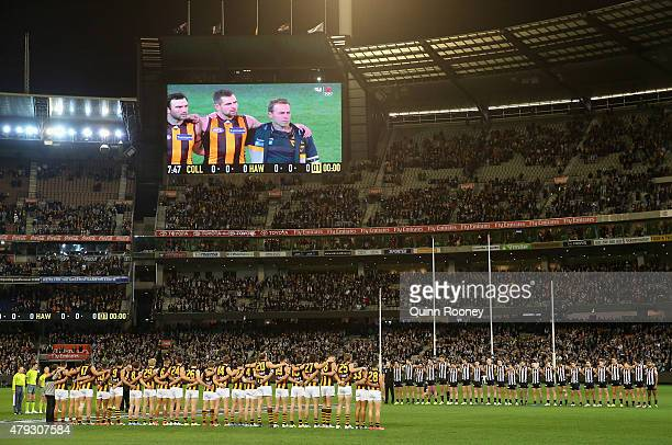 Team stand for a minute silence in rememberance of Phil Walsh during the round 14 AFL match between the Collingwood Magpies and the Hawthorn Hawks at...