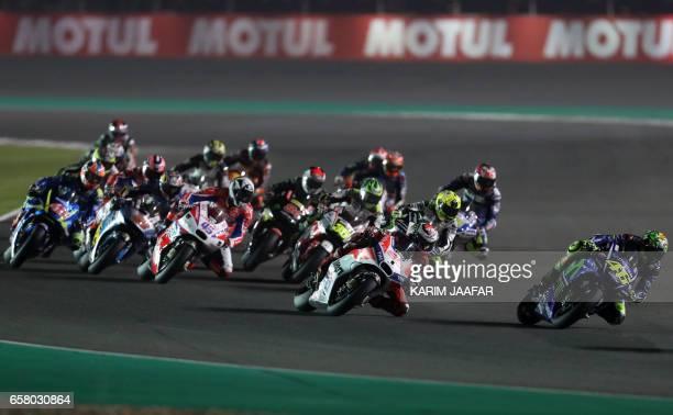 Team SUZUKI ECSTAR's Italian rider Valentino Rossi and Spanish Jorge Lorenzo of Ducati Team compete during the 2017 Qatar MotoGP at the Losail...