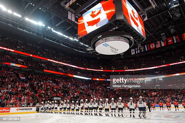 Team United States and Team Canada line up prior to the start of their match up while a Canadian flag is displayed on the screen in a preliminary...