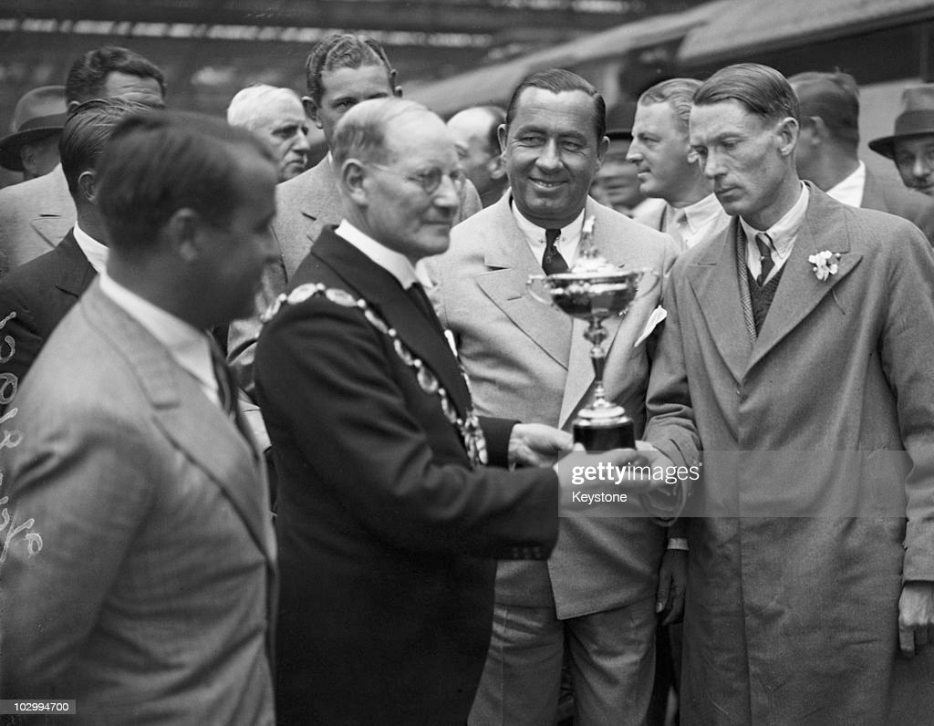 Team United States captain Walter Hagen (1892 - 1969, centre, right) hands the Ryder Cup to the Mayor of Southport on his team's arrival at Waterloo Station, London, 21st June 1933.