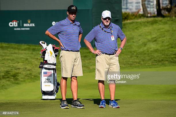 Team USA caddies Jim 'Bones' Mackay and Damon Green read putts on the 15th hole green during practice for The Presidents Cup at Jack Nicklaus Golf...