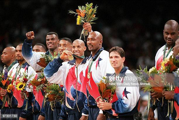 Team USA member Reggie Miller flashes his gold medal as he stands surrounded by other members of the United States men's basketball team during...