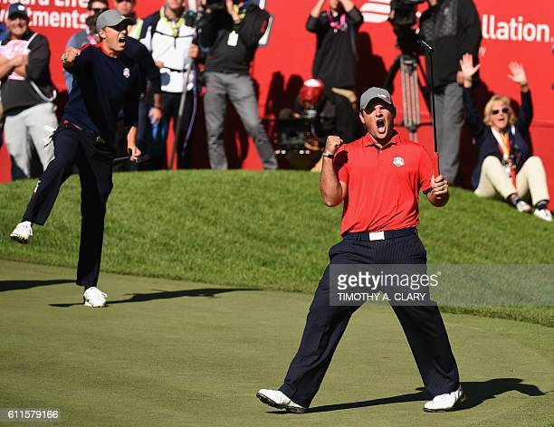 TOPSHOT Team USA Patrick Reed reacts with teammate Jordan Spieth after winning their match against Team Europe Justin Rose and Henrik Stenson on the...