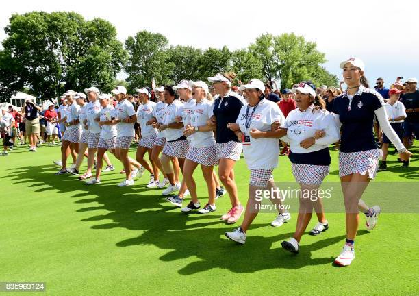 Team USA walk arm and arm up the 18th fairway after beating Team Europe 16 1/2 to 11 1/2 during the final day singles matches of the Solheim Cup at...