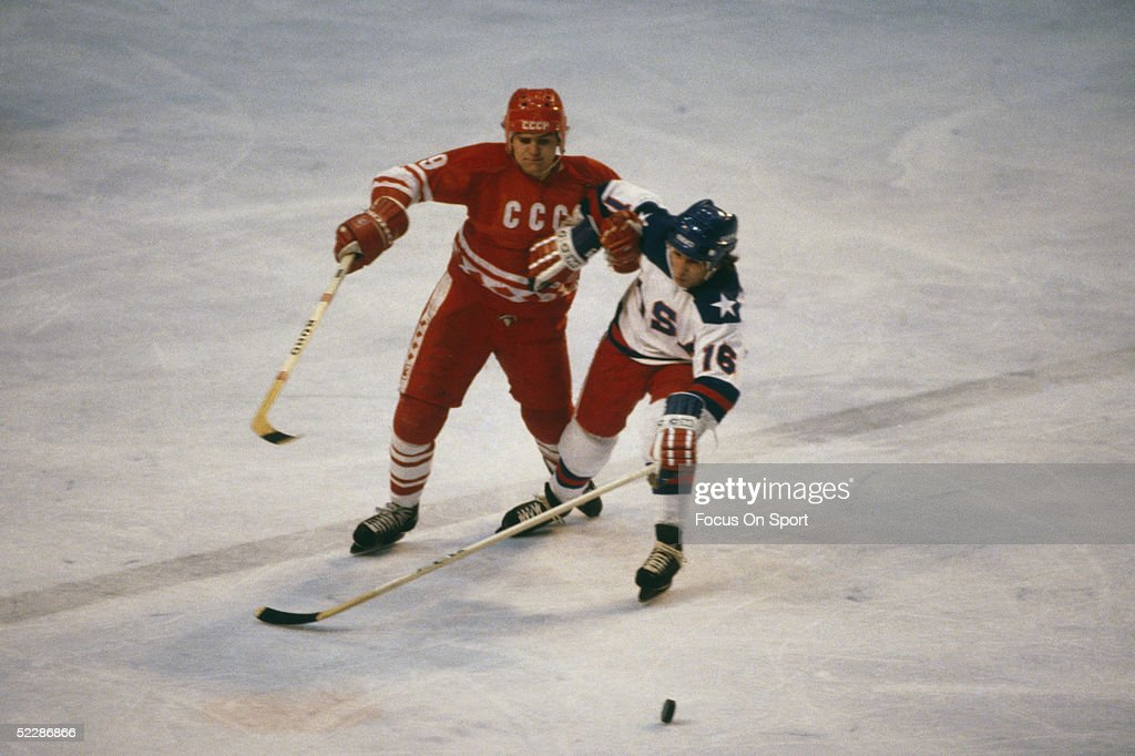 Team USA's Mark Pavelich struggles with Vladimir Krutov of the Soviet Union to gain control of the puck during the XIII Olympic Winter Games in...