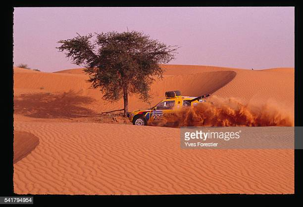 Teammates Ambrosino and Baumgartner drive their car a Peugeot 205 T16 through the Mauritanian desert during the 1990 Paris Dakar Rally NemaTidjika...