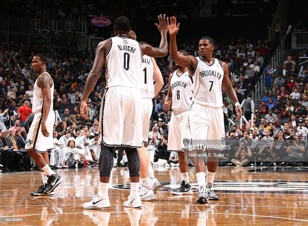 Teammates Andray Blatche #0 and Joe Johnson #7 of the Brooklyn Nets high five during a preseason game against the Miami Heat at the Barclays Center on October 17, 2013 in the Brooklyn borough of New York City.