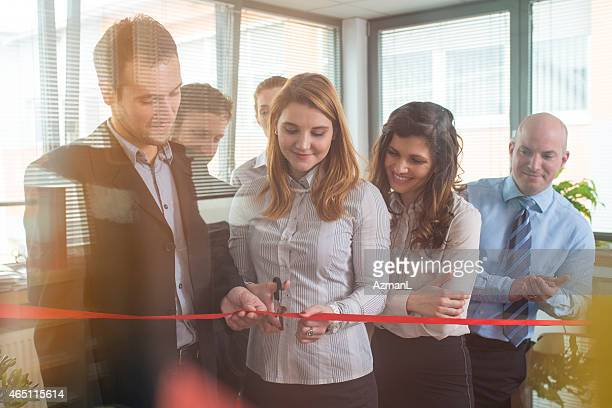 Teammates at an office cutting a ribbon for a new beginning