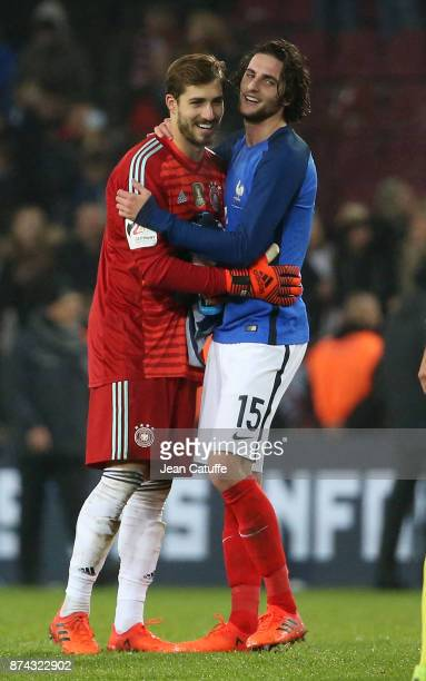 Teammates at Paris Saint Germain goalkeeper of Germany Kevin Trapp greets Adrien Rabiot of France following the international friendly match between...