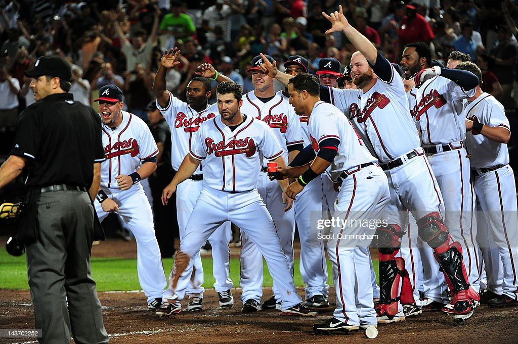 Teammates await <a gi-track='captionPersonalityLinkClicked' href=/galleries/search?phrase=Chipper+Jones&family=editorial&specificpeople=171256 ng-click='$event.stopPropagation()'>Chipper Jones</a> #10 of the Atlanta Braves at home plate after hitting a 11th inning walk off home run against the Philadelphia Phillies at Turner Field on May 2, 2012 in Atlanta, Georgia.