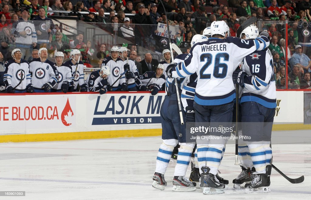 Teammates Blake Wheeler #26, Bryan Little #18, and Andrew Ladd #16 of the Winnipeg Jets celebrate a third period goal, during an NHL game against the Ottawa Senators, at Scotiabank Place, on March 17, 2013 in Ottawa, Ontario, Canada.