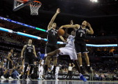 Teammates Brook Lopez and Deron Williams of the Brooklyn Nets knock the ball loose from Bismack Biyombo of the Charlotte Bobcats during their game at...