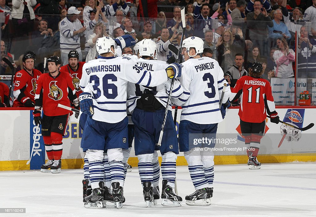 Teammates Carl Gunnarsson #36, Joffrey Lupul #19 and Dion Phaneuf #3 of the Toronto Maple Leafs celebrate a third-period goal during an NHL game against the Ottawa Senators, at Scotiabank Place, on April 20, 2013 in Ottawa, Ontario, Canada.