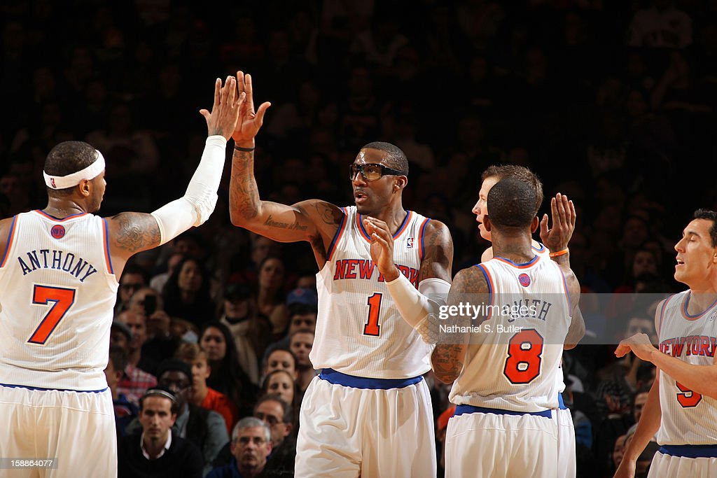 Teammates Carmelo Anthony #7, Amar'e Stoudemire #1, and J.R. Smith #8 of the New York Knicks celebrate during the game against the Portland Trail Blazers on January 1, 2013 at Madison Square Garden in New York City.